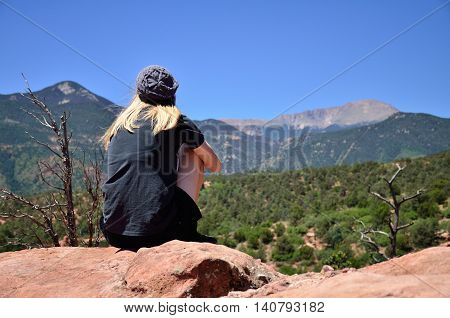 A teenage girl sits on a large red rock in the Garden of the Gods, looking at the distant Rocky Mountains.