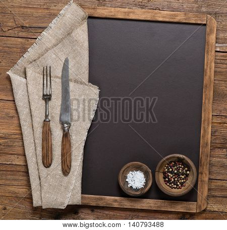 View from above of spices vintage spoon and fork on linen napkin on a blackboard on a rustic wooden table with copy space.
