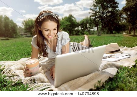 On the emotional wave. Cheerful charming delighted woman smiling and using laptop while resting on the grass