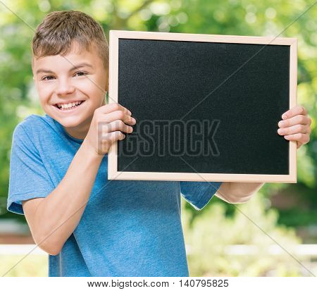 Outdoor portrait of happy teen boy 12-14 year old with small blackboard. Back to school concept.