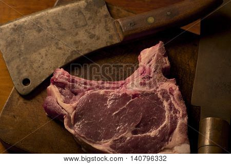 T-bone roast beef steak with a vintage cleaver on a cutting board
