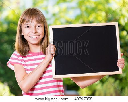 Outdoor portrait of happy girl 10-11 year old with small blackboard. Back to school concept.