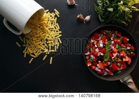 Ingredients for cooking pasta. Basil, tomato, pasta, garlic and onion on a wooden table