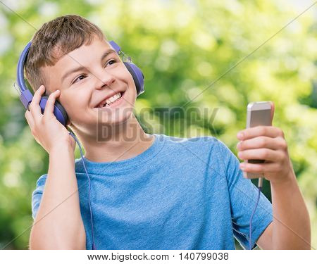 Outdoor portrait of happy teen boy 12-14 year old with cell phone - listening a music and sings in headphones