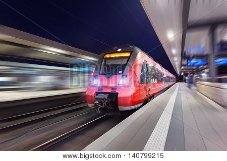 Modern High Speed Red Passenger Train Moving Through Railway Station