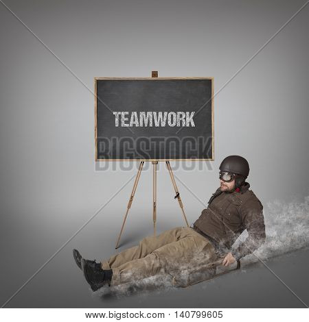 Teamwork text on blackboard with businessman sliding with a sledge