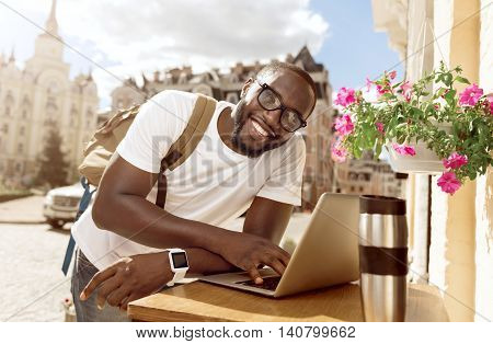 Positive thinker. Cheerful handsome smiling man leaning on the table and using laptop while standing outside the cafe