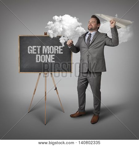 Get more done text on blackboard with businessman and paper plane