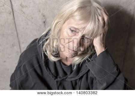 A depress senior person with concrete background