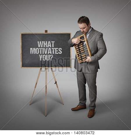 What motivates you  text on blackboard with businessman and abacus