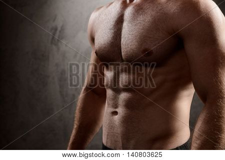 Close up photo of sportive man's body over dark background.