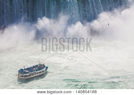 Niagara-Falls, Ontario, Canada - July 5, 2015: View of a tour boat, Maid of the Mist, navigating near the horseshoe falls in Niagara Falls, Ontario, Canada.