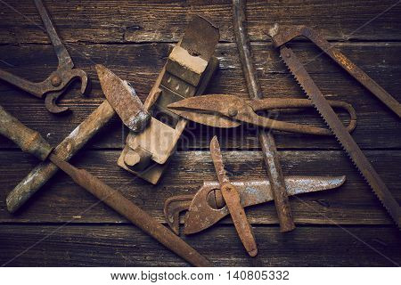 Grungy old rusted tools on a wooden background (cross-process)