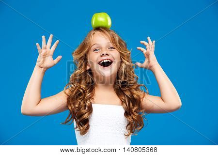 Young pretty girl holding green apple  on head, looking at camera, smiling over blue background.