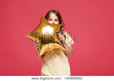 Young pretty girl holding baloons over pink background. Copy space.