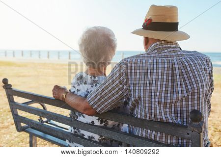 Senior Couple Sitting On A Bench At The Seaside