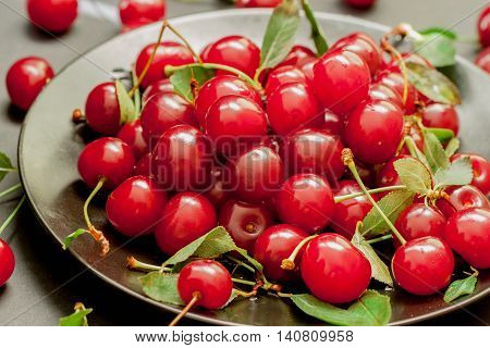 Black plate with delicious, juicy, bright cherries. Concept summer seasonal fruits