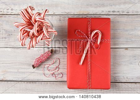 High angle view of a red paper wrapped Christmas present tied with string and a candy cane, next to a spool of twine and glass of candy canes.