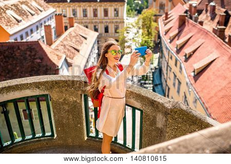 Young female traveler making photo with smart phone standing on the Schlossberg stairs on the cityscape background in Graz town. Traveling in Austria