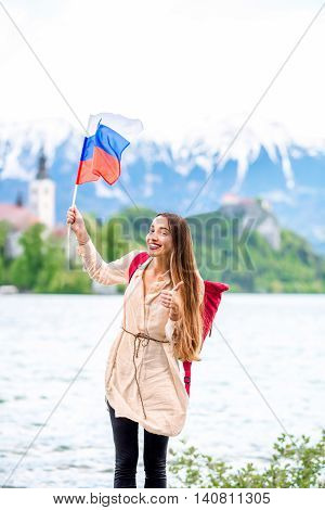 Young female tourist with slovenian flag standing near Bled lake, popular tourist destination in Slovenia. Promoting tourism in Slovenia
