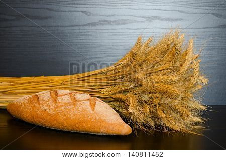 Whole grain bread and a sheaf on a dark background