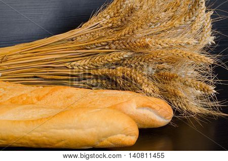 White loaves and a sheaf on a dark background close-up