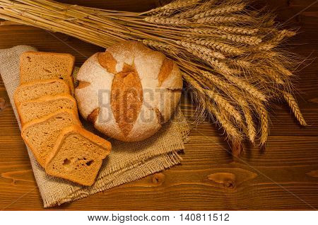 Round and square of rye bread on a sacking a sheaf on wooden table top view