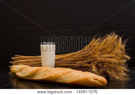 A glass of milk a loaf and a sheaf on a black background with space for text
