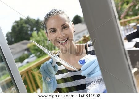 Homehelp cleaning house windows with squeegee
