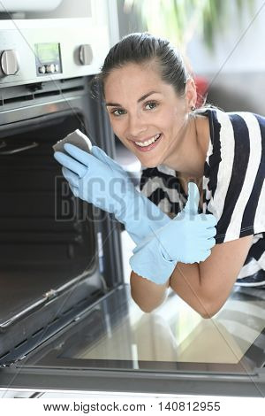 Young woman in kitchen cleaning oven