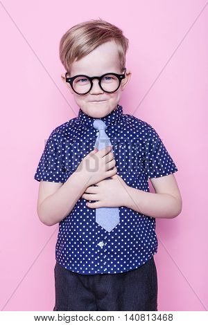Portrait of a little smiling boy in a funny glasses and tie. School. Preschool. Fashion. Studio portrait over pink background
