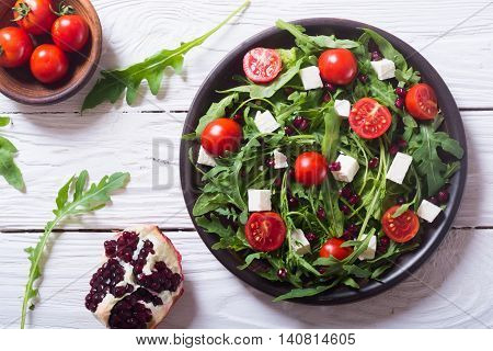 Fresh spring salad with rucola feta cheese tomatoes and pomegranate seeds