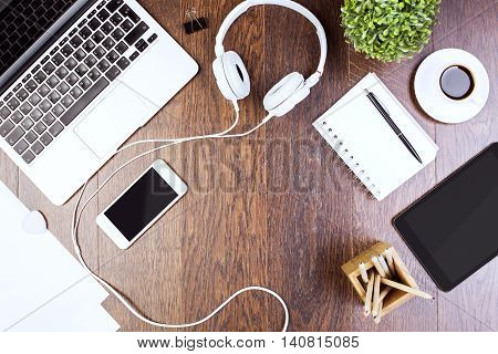 Top view of wooden desktop with tablet laptop smartphone headphones decorative plant and supplies. Mock up