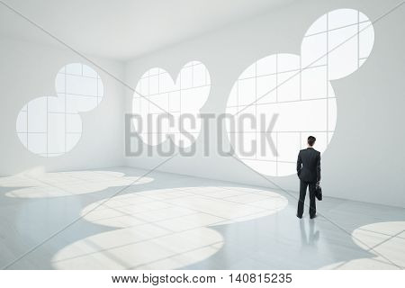 Thoughtful businessman in abstract white interior with round windows sunlight and shadows. 3D Rendering