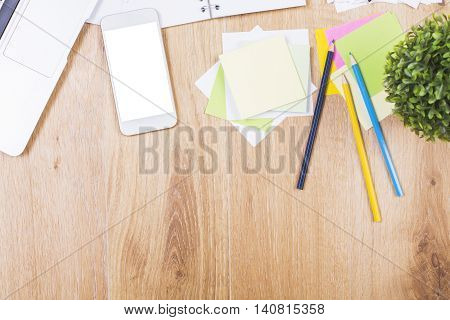 Top view of wooden office desktop with blank white cellular phone plant and variety of colorful supplies. Mock up