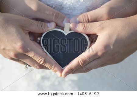 bride and groom holding black heart a board in the form of heart