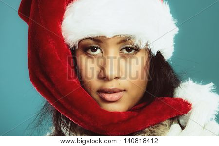 Christmas winter happiness concept. Young woman girl mixed race wearing santa helper hat portrait. Blue background