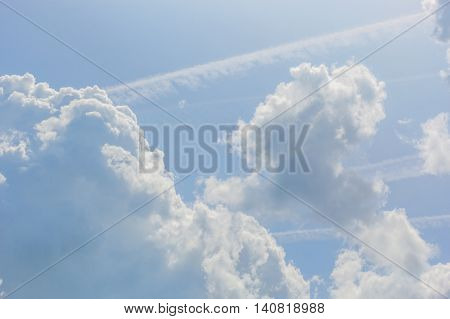 Blue sky with white cumulus clouds and contrails on a sunny summer day