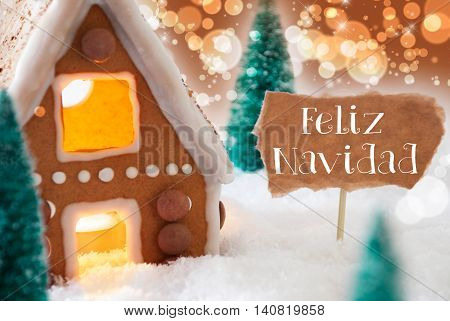 Gingerbread House In Snowy Scenery As Christmas Decoration. Christmas Trees And Candlelight. Bronze And Orange Background With Bokeh Effect. Spanish Text Feliz Navidad Means Merry Christmas