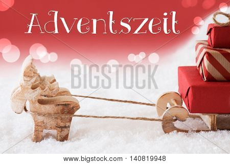 Moose Is Drawing A Sled With Red Gifts Or Presents In Snow. Christmas Card For Seasons Greetings. Red Christmassy Background With Bokeh Effect. German Text Adventszeit Means Advent Season