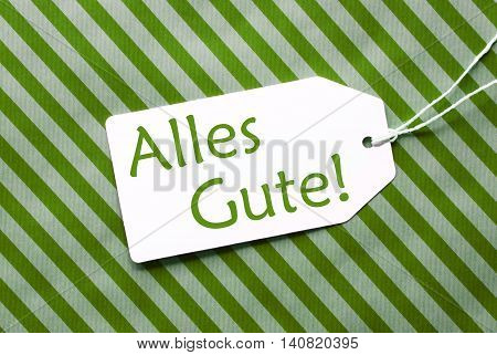One Label On A Green Striped Wrapping Paper. Textured Background. Tag With Ribbon. German Text Alles Gute Means Best Wishes