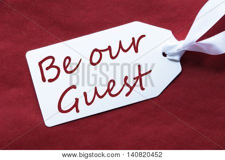 One White Label On A Red Textured Background. Tag With Ribbon. English Text Be Our Guest