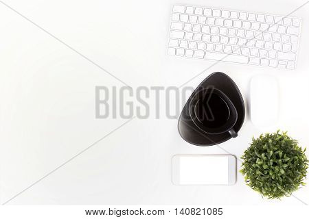 Top view of bright white office desktop with computer mouse keyboard coffee cup blank cellular phone and decorative plant. Mock up