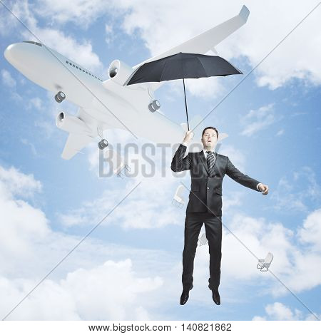 Man with umbrella falling out of airplane on bright blue sky background