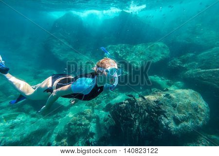Young lady snorkeling over coral reefs in a tropical sea. Similan Islands in Thailand, one of the tourist attraction of the Andaman Sea.