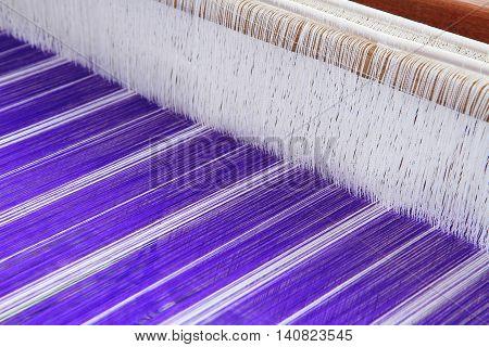 Close up of blue yarn silk on loom weaving