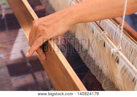 Woman hand weaving pattern on traditional loom
