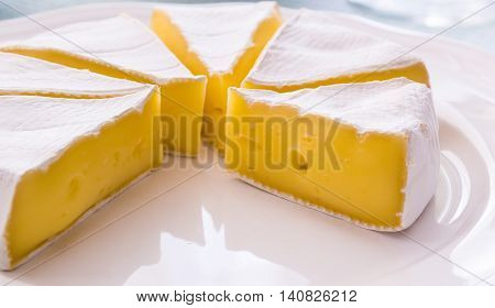Sliced yellow cheese on a white plate