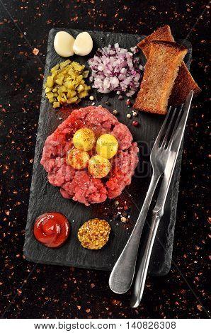 Steak tartare on black stone plate on marble tabletop