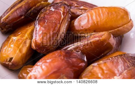 Closeup dried candied dates on white plate